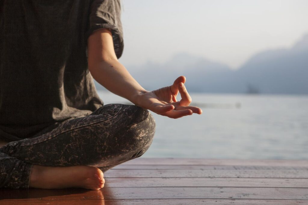 A female sits by a lake meditating because she knows how to handle hard inerview questions