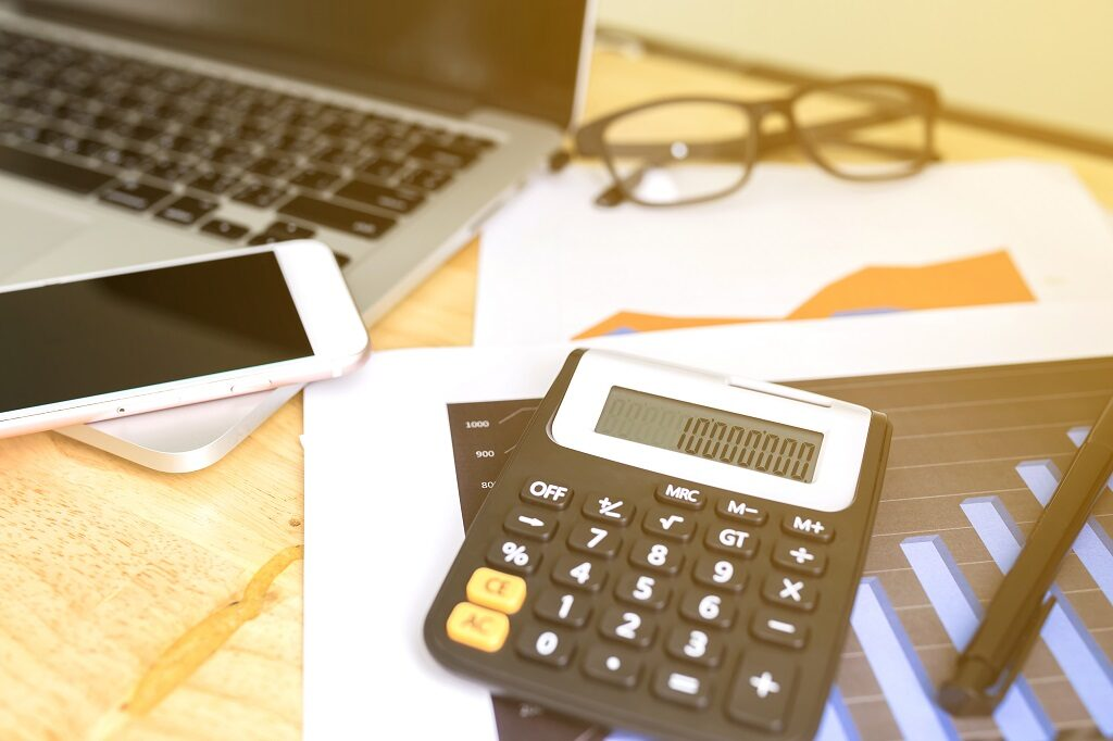 A laptop, mobile phone, calculator, and reports - the tools of the accounting trade