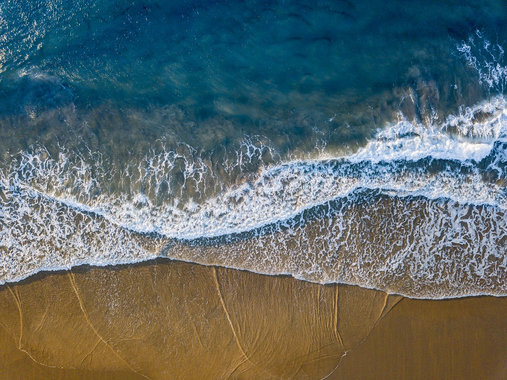 An aerial view of the sea and waves on a sandy beach.