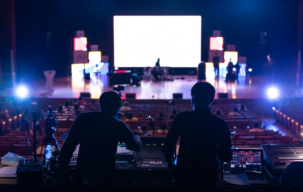 Sound engineers get ready to test the audio system at an event while the events manager checks the stage.