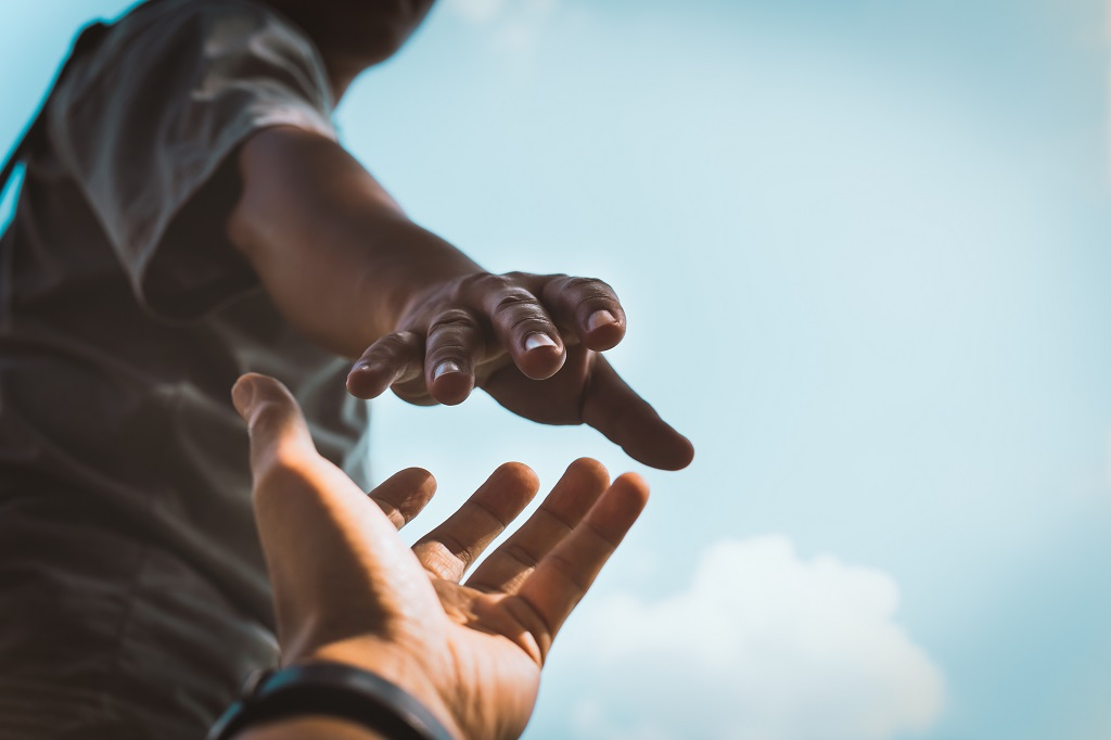 A charity worker's hand reaches out to support someone in need.
