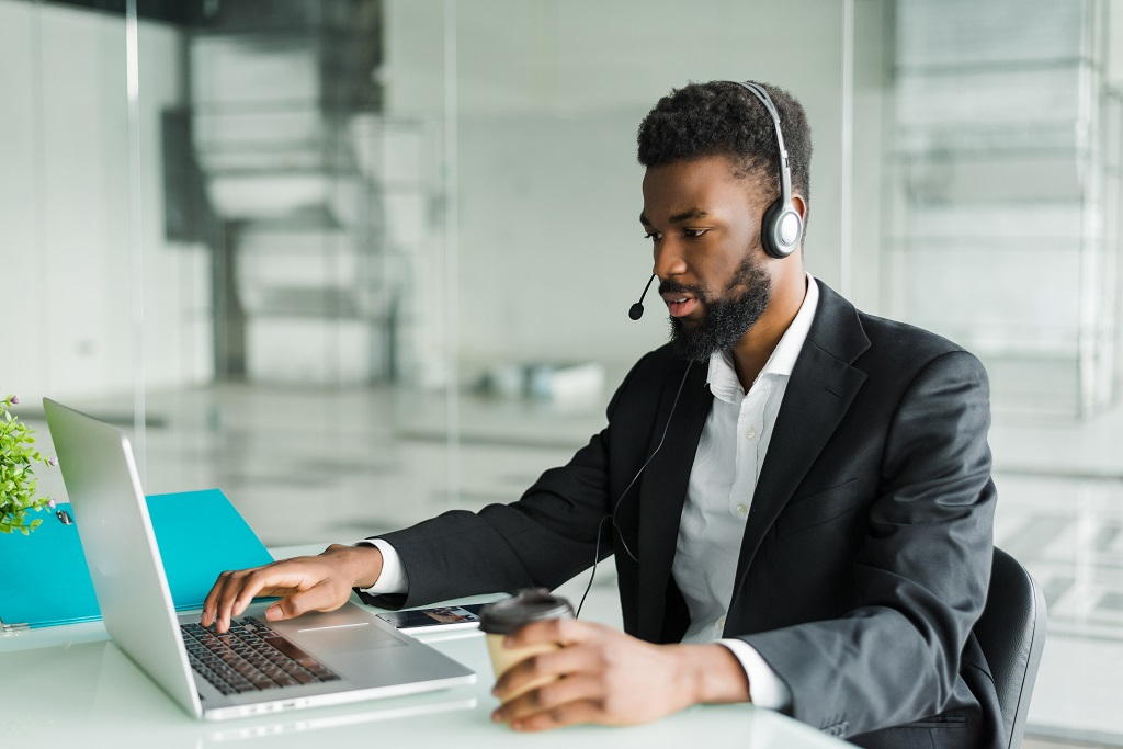 A customer support agent working at thier laptop with a headset.