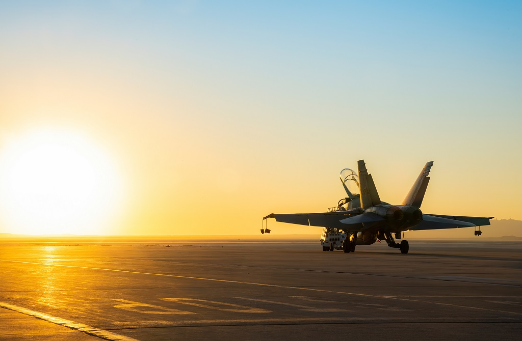 A fighter jet taxis on the runway of an aircraft carrier ready to launch at sunset.